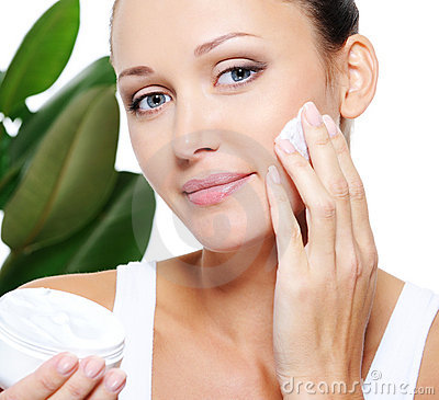 Woman holding moisturizer and applying it on face
