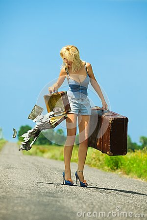 Woman holding  opening suitcases with cash
