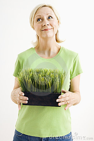 Woman holding potted grass.