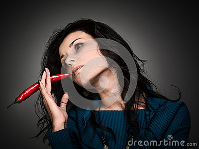 Woman holding red hot chili pepper in mouth