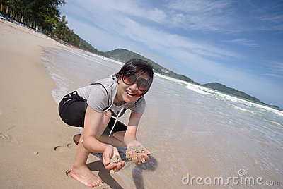 Woman holding sand on beach