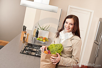 Woman holding shopping bag with grocery in kitchen