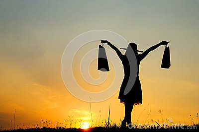 Woman holding shopping bags in sunset silhouette