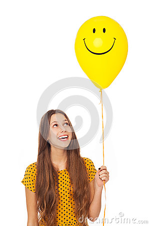 Woman holding smiley face balloon
