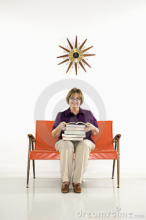 Woman holding stack of books.