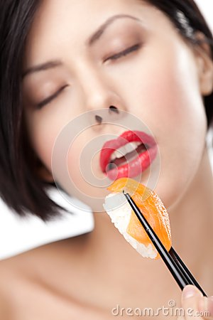 Woman holding sushi with a chopsticks, closeup