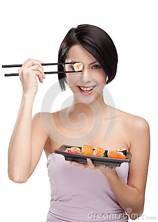 Woman holding sushi roll with a chopsticks