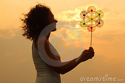 Woman holding toy whirligig at sunset