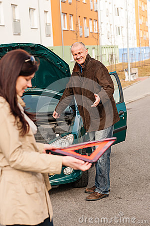 Woman holding triangle sign repairman fixing car