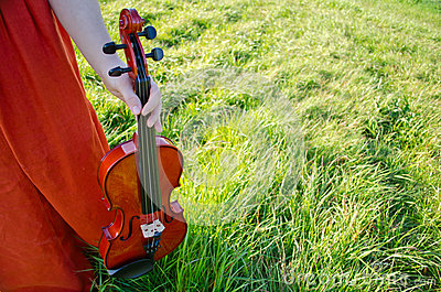 A woman holding a violin in nature horizontal
