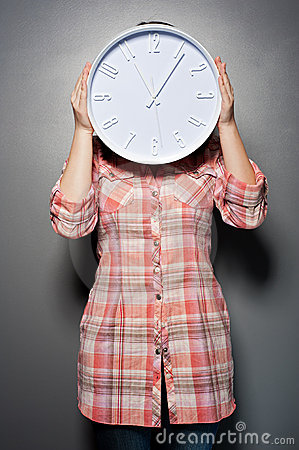 Woman holding wall clock infront of her face