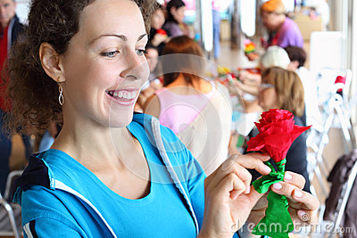 Woman holds artificial red rose