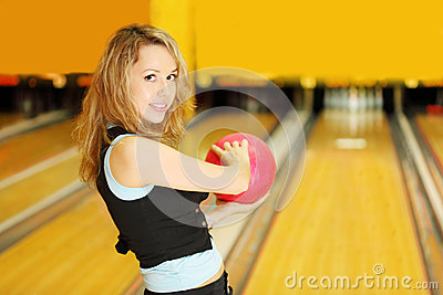 Woman holds ball and prepares to throw in bowling