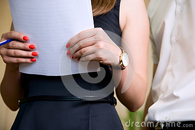 Woman holds document and man nearby