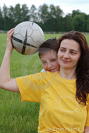 Woman holds football, boy peeps out