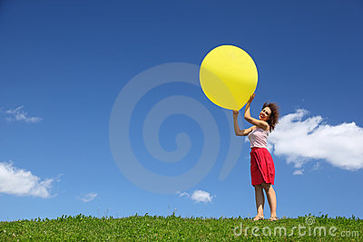 Woman holds large ball in hands on wind
