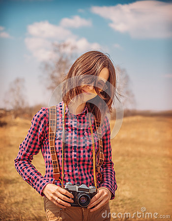 Woman holds old photo camera on nature