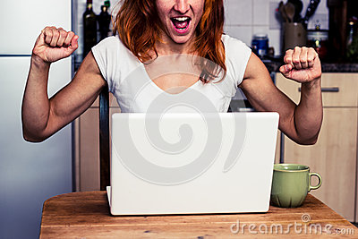 Woman at home is very excited about her laptop