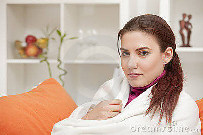 Woman at home wrapped in blanket