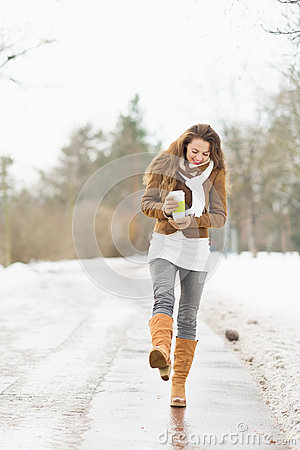 Woman with hot beverage walking in winter park