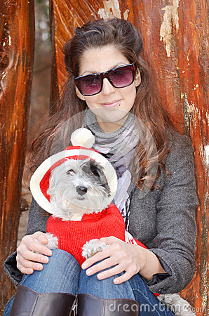 Woman hugging her dog dressed with red christmas hats
