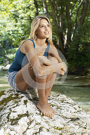 Woman Hugging Knees While Looking Away By Forest River