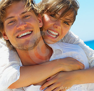 Woman hugging young man at the beach