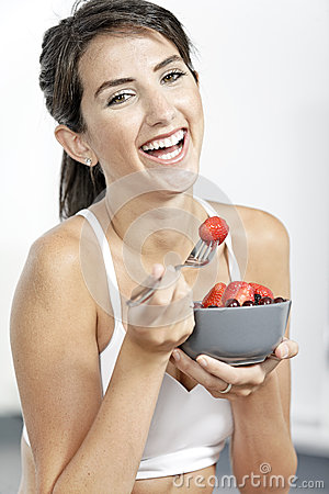Woman ieating fruit in fitness clothes
