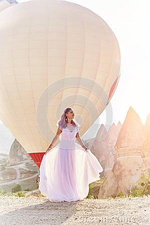Free Woman In A Long Dress On Background Of Balloons In Cappadocia. Girl With Flowers Hands Stands On A Hill And Looks At Large Number Stock Photography - 121350582
