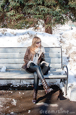Free Woman In A Winter Park Sits On A Bench Stock Images - 19880474