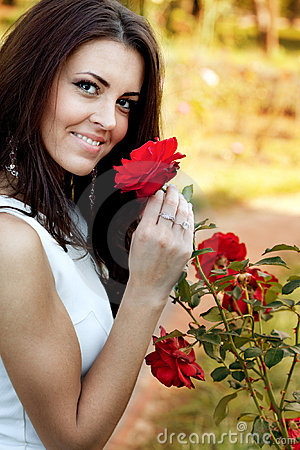 Free Woman In Flower Garden Smelling Red Roses Stock Photo - 13755220