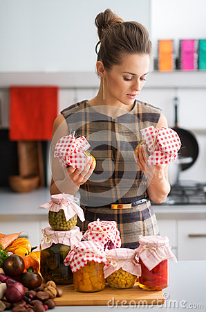 Free Woman In Kitchen Holding Preserves And Looking At Jars Stock Images - 60752974