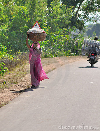 Woman in India carries basket on her head Editorial Stock Image