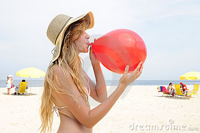 Woman inflating a red balloon on the beach