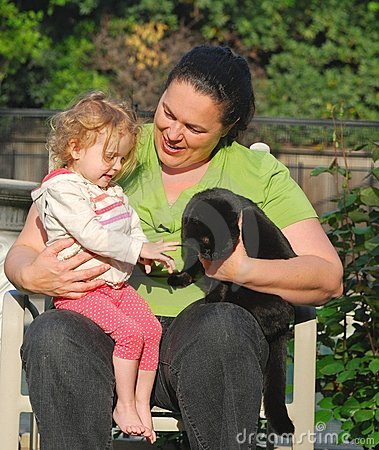 A woman introduces a toddler to a black cat