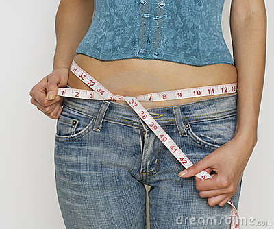 Woman in jeans measuring waist