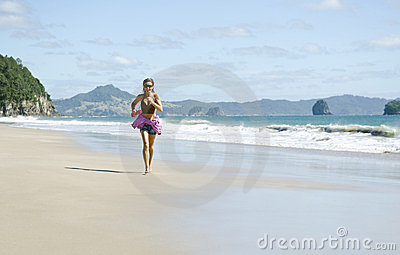 Woman jogging along a beautiful beach.