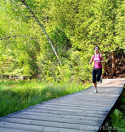 Woman Jogging on a Boardwalk in the Forest