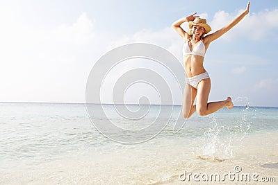 Woman Jumping In The Air On Tropical Beach