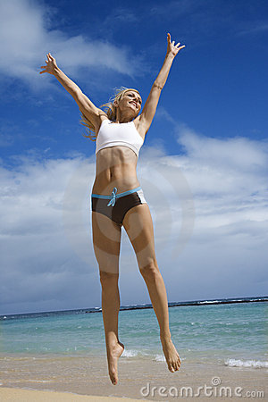 Woman jumping on beach.