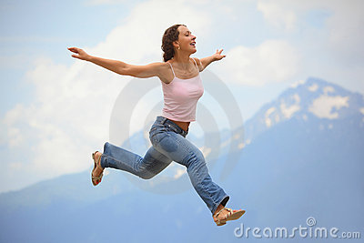 Woman is jumping with hands wide apart