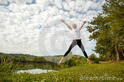 Woman jumping by the lake