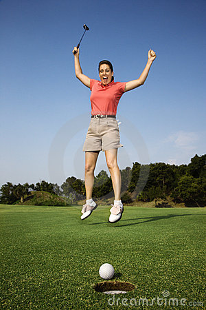 Woman jumping over good golf shot.