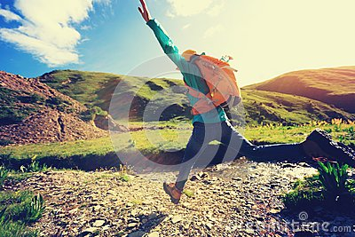 Woman jumping over high altitude river Stock Photo