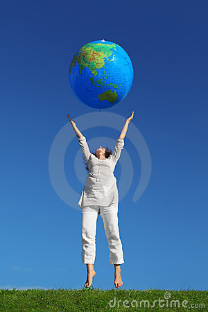 Woman jumping and throwing inflatable globe Stock Photo