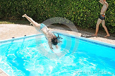 Woman jumping to swimming pool