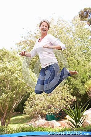 Woman Jumping On Trampoline In Garden