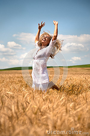 Woman jumping in wheat field