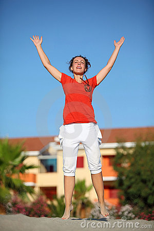 Woman jumps on beach and lifts hands to sky
