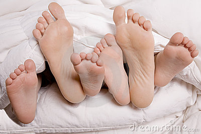 Woman and kids feet in bed